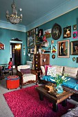 Many different framed pictures of women on turquoise wall in renovated, vintage-style period apartment