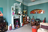 White-painted, nostalgic fire surround with mirror decorated with hotchpotch of flea market finds in open-plan living area