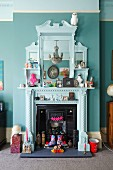 White-painted, nostalgic fire surround with mirror decorated with hotchpotch of flea market finds