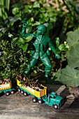 Loaded toy truck on weathered wooden board next to toy soldier in garden