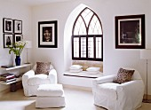 Armchairs and footstool with white loose covers in corner of room in front of Gothic window niche with window seat