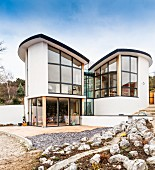 Architect-designed house consisting of two rounded structures with singe-pitch roofs built into slope; large windows with views over incomplete gardens