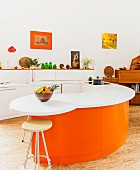 Curved breakfast bar with Corian worksurface and bright orange base units in open-plan designer kitchen