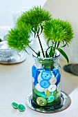 Vase of flowers decorated with buttons in water