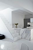 Weisser Treppenaufgang vor Marmor Küchenblock mit Spüle, im Vordergrund teilweise sichtbare Drahtgestell Stühle an rundem Tisch