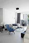 Fifties reading chair with blue cover in front of round coffee table and comfortable sofa in living room