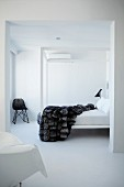 White, minimalist bedroom with fur blanket on canopied bed; Bauhaus wicker chair in corner