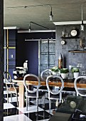 Vintage dining area with antique, Victorian chairs with backrest cushions removed, industrial lamps and dark-painted walls with stucco frieze