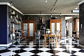 Antique, Victorian elements and industrial style in open-plan interior with reflective chequered floor tiles and dark grey marbled walls