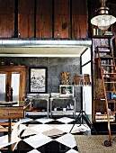 Warm wood hues and industrial elements in corner of interior with glossy, chequered floor