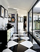 Sideboard decorated with collectors' items and gallery of pictures in hallway with elegant, chequered floor and glass wall with view of courtyard on right