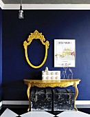 Yellow console table and escutcheon-shaped, empty mirror frame on royal blue wall