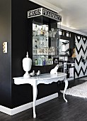 White console table against black wall below collection of apothecaries' bottles in glass case with lettered sign