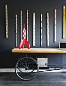 Tintin rocket on upcycled table with wheels below collection of old rulers hanging on dark wall