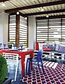 Roofed terrace with old table, collection of chairs and rug with red, white and blue pattern in front of armchairs upcycled from old pallets with scatter cushions