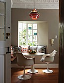 Classic, white swivel chairs and round table in front of bench with many scatter cushions below classic pendant lamp hanging from stucco ceiling