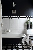 View through open door into black and white bathroom - vintage bathroom on chequered floor against half-height tiled wall separated from black upper wall by border