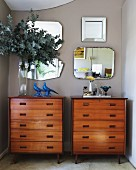 Vase of leaves on one of two wooden chests of drawers against pale grey wall with collection of vintage mirrors