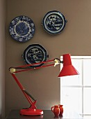 Red, metal desk lamp against wall painted pale grey with collection of traditional, blue and white plates