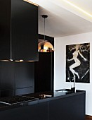 Black kitchen counter with sink and hob below extractor hood next to pendant lamp with copper-coloured lampshade