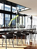 Long dining table and chairs with high backrests next to steel and glass facade in penthouse apartment