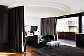 Bed and couch below circular ceiling element with integrated curtains and lights next to floor-to-ceiling window