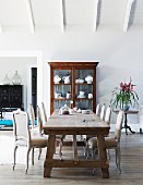 Dining area with antique, French, upholstered chairs and rustic dining table in front of white china in display cabinet