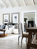 Living area in elegant country-house style with antique dining chairs and comfortable sofa