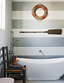 Modern bathroom with free-standing bathtub and maritime decorations on grey and white striped wall
