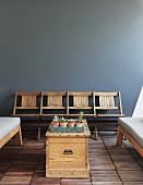 Alte Kinostühle an blauer Wand; im Vordergrund eine einfache Holztruhe zwischen gepolsterten Sitzbänken