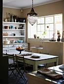 Einfache Küche mit langem Holztisch, einem Geschirrschrank im Vintagelook und einer gemauerten Spüle unter dem Fenster