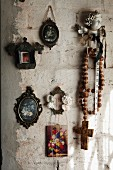 Miniature pictures of flowers and rustic rosary on roughly plastered wall