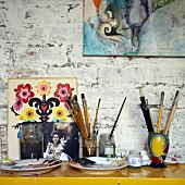 Painting utensils on console table and pictures leaning against and hung on wall
