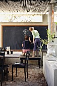 Veranda with vintage furniture and two children drawing on large blackboard