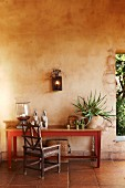 Rustic wooden chair and simple table against wall next to window-style aperture in rustic loggia