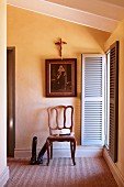 French, oak chair below religious painting and crucifix next to window with open shutters