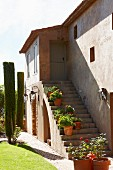 House with potted flowering plants on exterior staircase in sunshine and clipped cypresses in garden