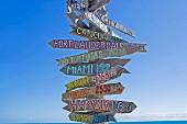 Holz Wegweiser mit gemalten Ortsnamen vor blauem Himmel