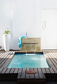 Spa area with wooden decking and sunken pool with waterfall