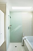 Modernes Bad mit bodenebener Dusche vor Badewanne und Oberlicht in Decke