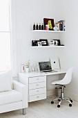 Arbeitsecke - weisser Drehstuhl vor Schreibtisch mit Schubläden und Bords an Wand neben Sessel vor Fenster