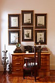 Antique, dark wood chair at desk with drawers below framed pictures on wall