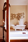 Screen with window next to doorway and view of free-standing, vintage bathtub in minimalist bathroom with Oriental motif on wall