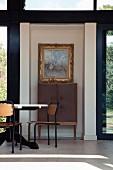 Tisch und Stühle im Retro Stil vor Schrank mit Füssen an Wand zwischen Terrassentüren