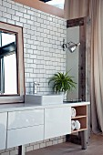 Washstand with white base cabinet on metal legs against tiled wall
