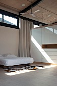 Sleeping area with double bed and cow-skin rug next to wardrobe functioning as partition in contemporary house with transom windows