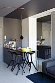 Black breakfast bar and bar stools next to entrance door in modern apartment; mirrored wall enlarges the room