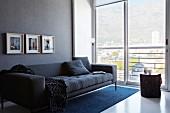 Moderne, anthrazitfarbene Couch an grauer Wand; neben der Couch eine raumhohe Glasfront mit herrlichem Blick auf das Häusermeer und die Berge