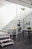Wide, airy staircase in open-plan interior with designer plexiglass chairs and black dining table; black and white graphics on wall
