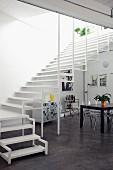 Breiter, luftiger Treppenaufgang in offenem Wohnraum mit Designerstühlen aus Plexiglas und einem schwarzen Esstisch; an der Wand schwarz-weisse Grafik